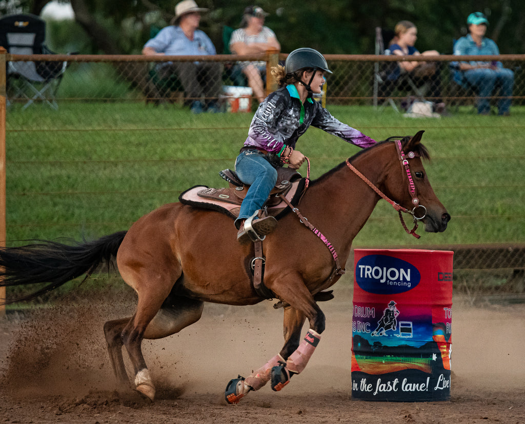A girl riding a brown horse wearing red Scoot boots in a barrel race competition