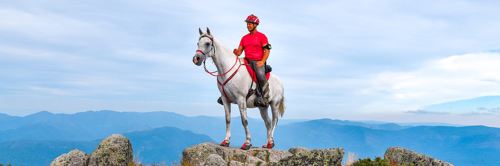 A man wearing red riding a white and grey horse wearing red Scoot Boots on a rock in the mountains