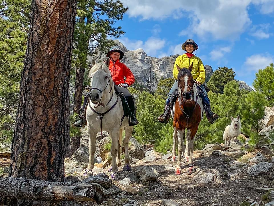 A woman and her daughter riding horses wearing Scoot Boots in the forrest in front of Mt. Rushmore