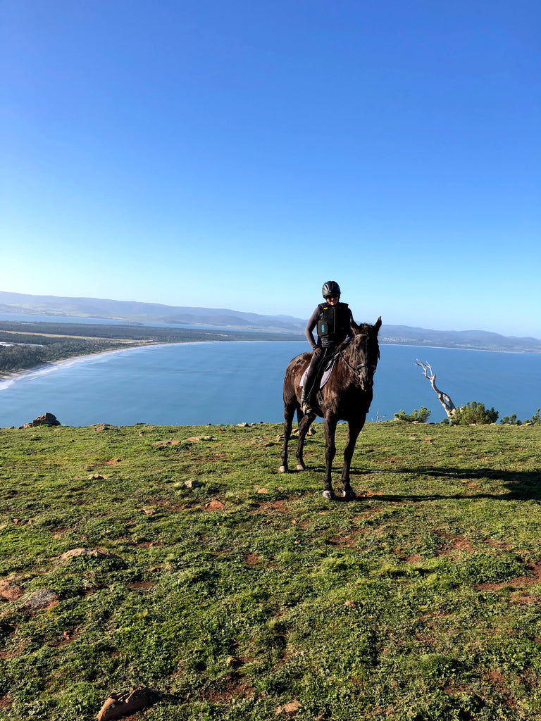 A woman riding a black horse wearing Scoot Boots on a grassy mountain in front of a beach and bright blue sky