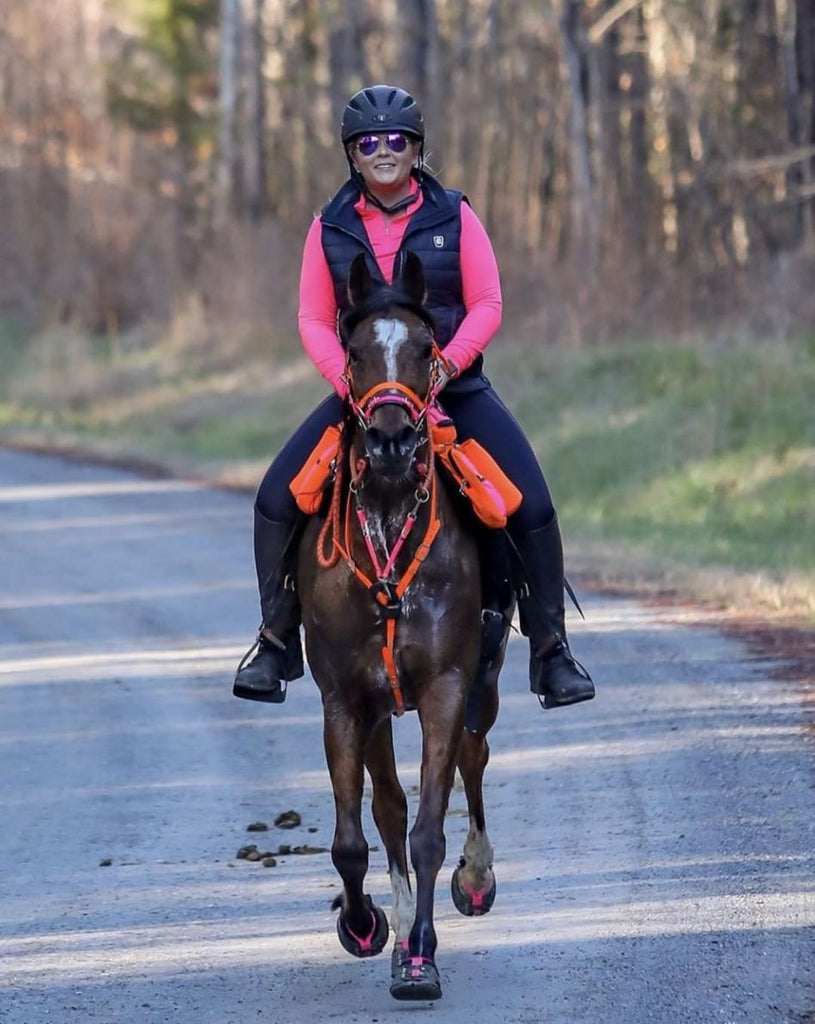 A woman wearing orange and pink riding a brown endurance horse in pink Scoot Boots