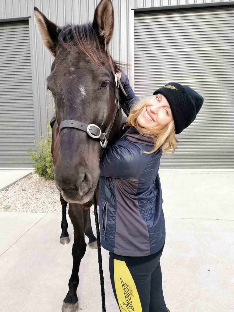 Annette Kaitinis wearing yellow Scoot Boot tights hugging her black horse in her driveway