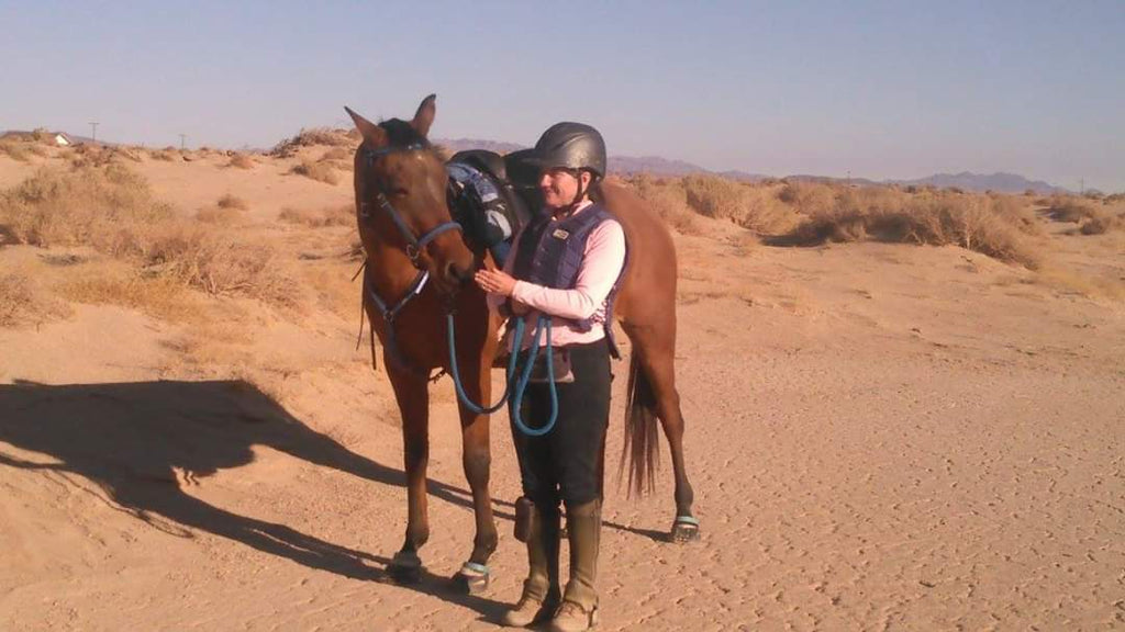 Woman petting her brown horse wearing blue Scoot Boots in the desert