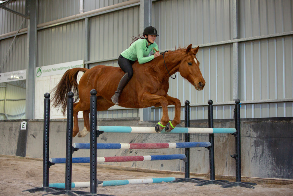 Girl in a green jacket jumping a brown horse wearing green Scoot Boots over jumping poles in a sand arena