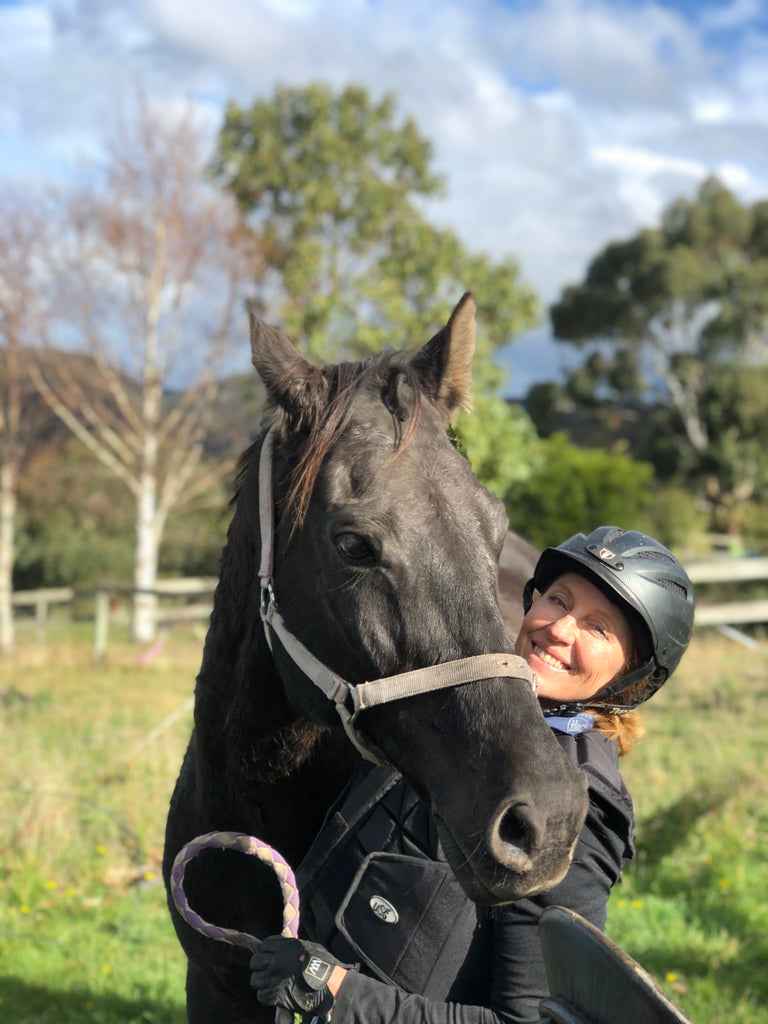 Annette Kaitinis posing with her black horse Matty in Tasmania