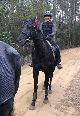 A woman riding her black horse on a trail ride in Tasmania