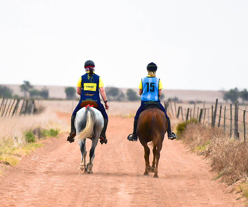 Riders riding down a dirt road in a horse riding competition in Scoot Boots