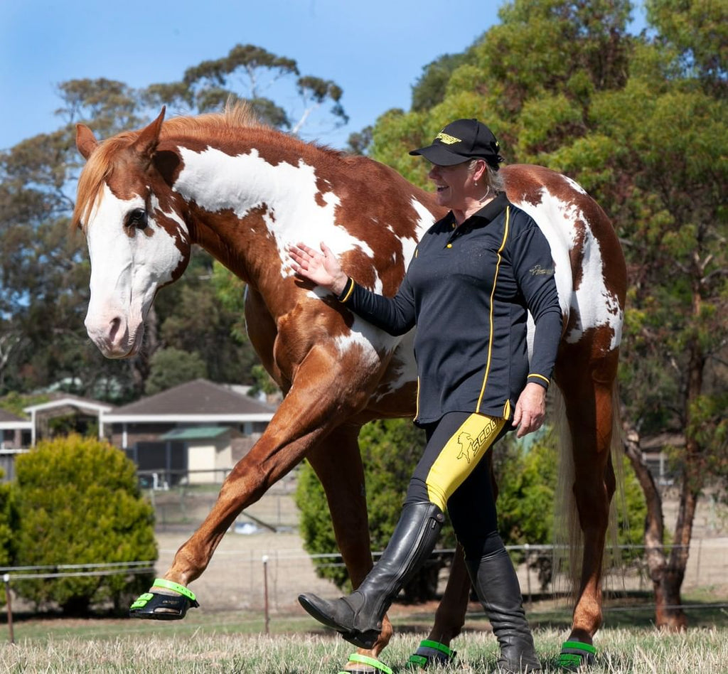 Woman and paint horse wearing green Scoot Boots walking in a paddock