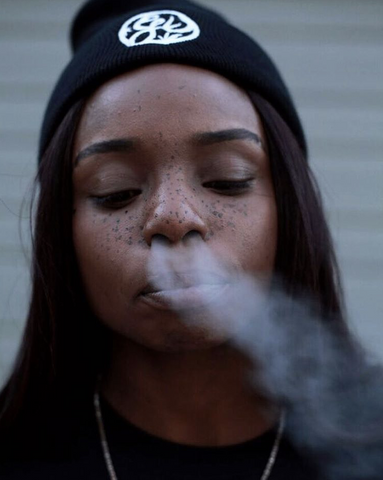 Woman wearing beanie, blowing smoke