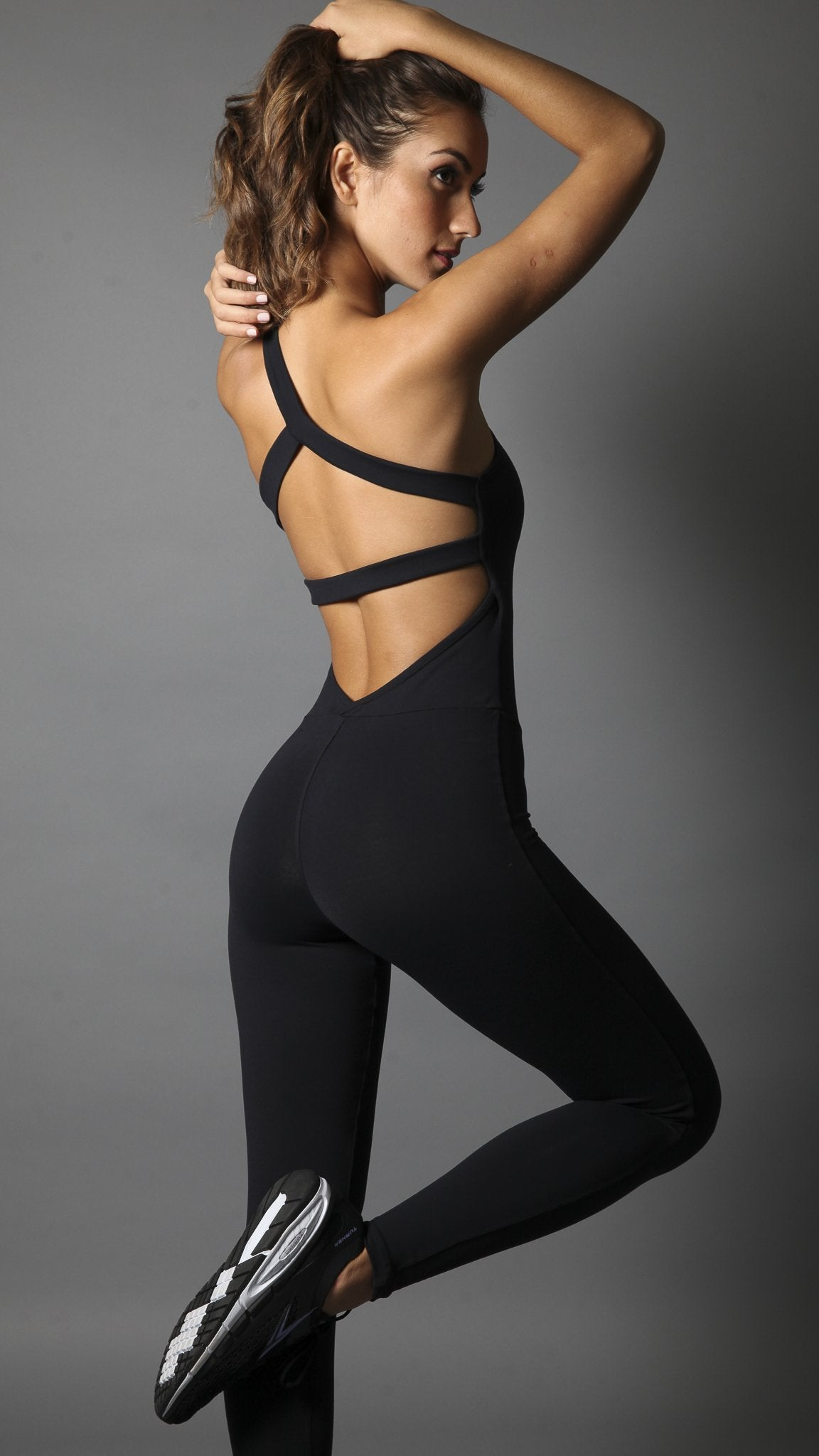 Black open back with wide elastic band on one shoulder and breast for support