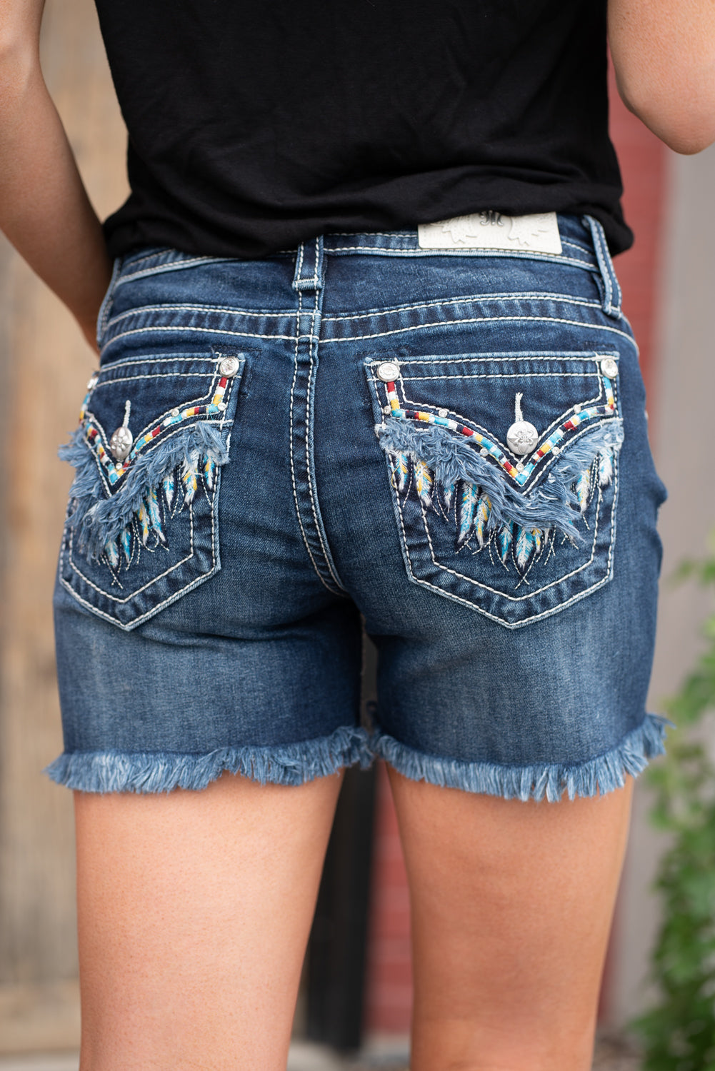 "Miss Me Jeans Collection: Summer 2020 Name: Fringe Feather Color: Dark Wash Cut: Shorts, 3"" Inseam Rise: Mid Rise, 8.75"" Front Rise 93% Cotton, 5% Polyester, 2% Elastane Stitching: Classic Fly: Zipper Style #: M3593H"