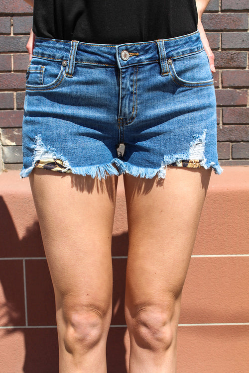 "Kan Can Jeans  Be wild this summer! These leopard patch shorts are sure to impress, everyone will want them. Pair with a chunky wedge and your favorite t. Collection: Spring 2020 Color: Medium Wash Material: 98% COTTON 2% SPANDEX Cut: Shorts, 2.5"" Inseam Rise: Low Rise, 2.5"" Front Rise Style #: KC6240M Contact us for any additional measurements or sizing."