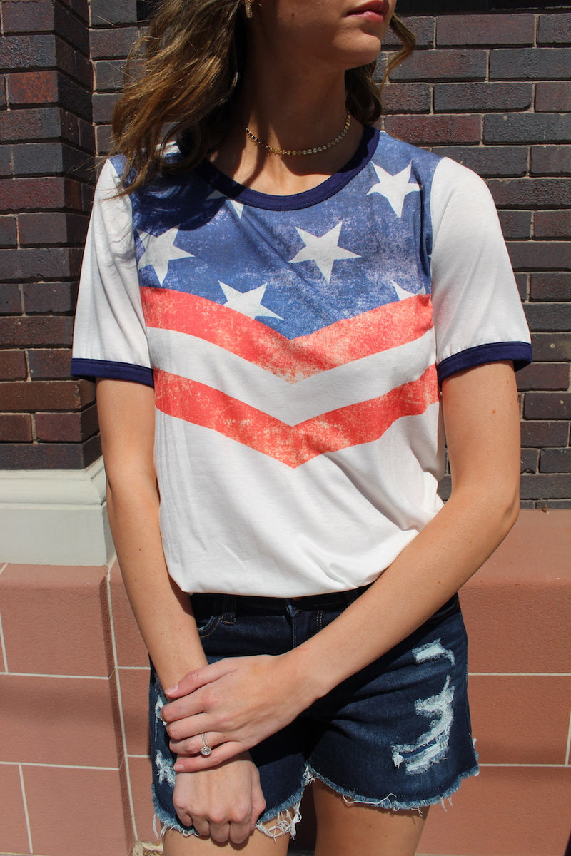 Be patriotic all summer long! Pair this cute americana t-shirt with your favorite shorts for a fun casual look.   Collection: Spring 2020 Style Name: American Honey Color: White Cut: Short Sleeve Material: 87% Poly 10% Rayon 3% Spandex Style #: BT1042 Contact us for any additional measurements or sizing.  Mckenna is 5'10