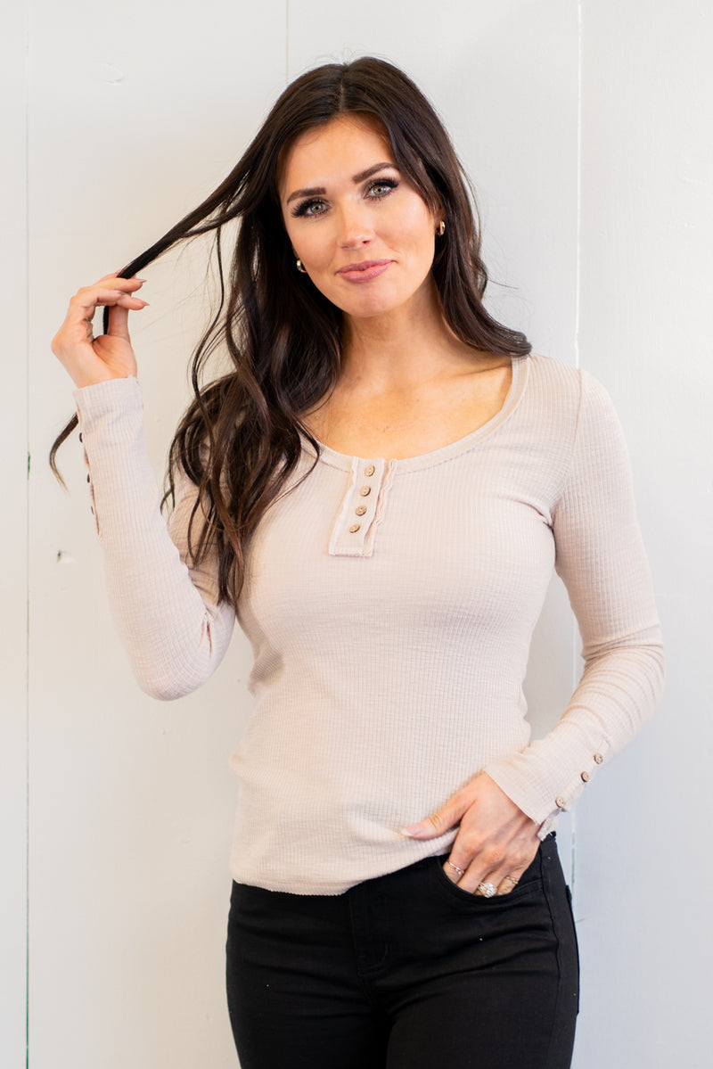 "This long sleeve Henley top is great for layering up or down during winter and pairs well with any denim.  Collection: Springe 2021 Color: Beige Button Up Front Henley with Button Sleeve Detail Neckline: Round Sleeve: Long Sleeve Self - 60% POLYESTER/32% COTTON/8% SPAN Style #: HUT7409-K18-Beige Chloe is 5'8"" and 130 pounds. She wears a size 3 in jeans, a small top and 8.5 in shoes. She is wearing a small in this top."
