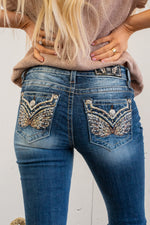 "Miss Me  These Chloe Boot cuts feature fading and whiskering details, metallic gold threads, multicolored rhinestone gems, and intricate embroidery. Collection: Spring 2021 Wash: Dark Wash Inseam: 34"" Inseam Material: 98% Cotton, 2% Elastane Sequin Trim and Rhinestone Rivets  Mid Rise, 8.75"" Front Rise Embellished Feather Pocket Style #: M3080B21 Contact us for any additional measurements or sizing.  Haley wears a size small top, a 25 in jeans and a small in tops. She is wearing a size 25 in these jeans."