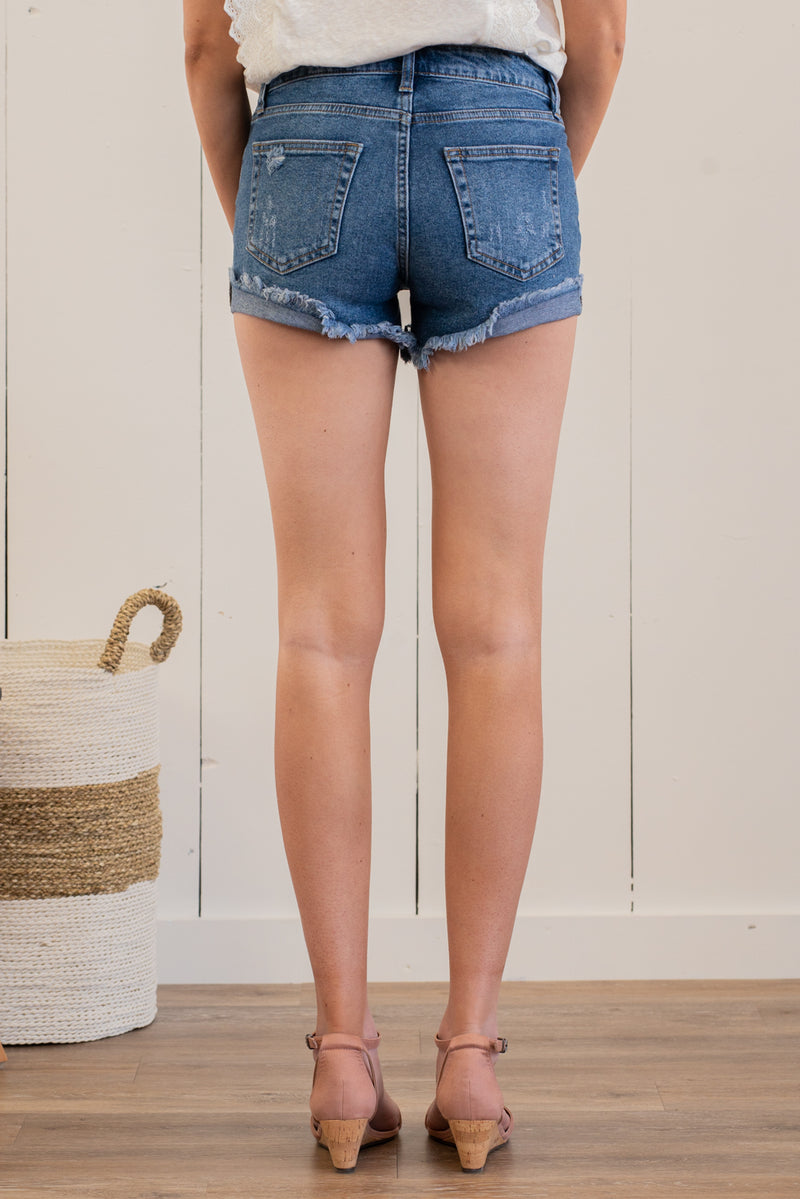 "Just USA Jeans  Color: Medium Blue Cut: Shorts, 3"" Inseam Mid Rise, 9"" Front Rise   Stitching: Classic 95% Cotton 4% Polyester 1% Spandex Fly: Zipper Style #: JH201-MD Contact us for any additional measurements or sizing.   Mckenna is 5'10"" and 122 pounds. She wears a size small top, a 4 in jeans and a size 8.5 in shoes. She is wearing a size small in these shorts."