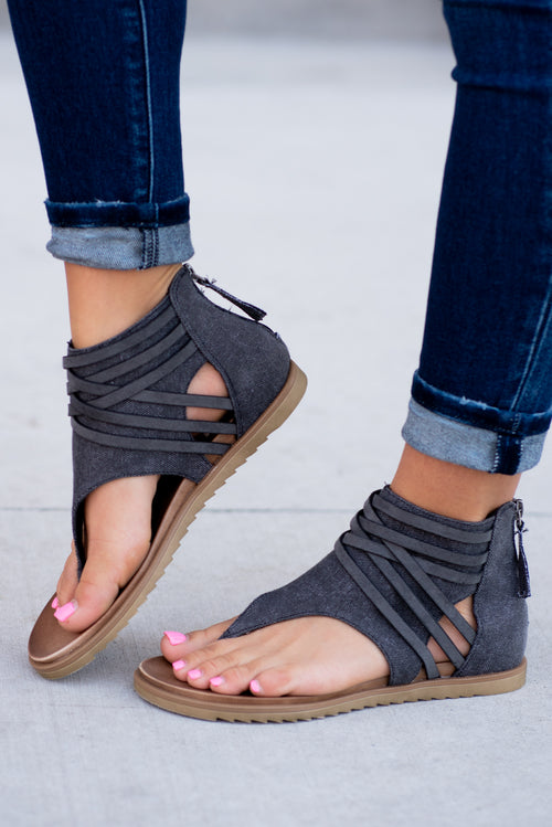 Strappy Sandal by Very G  These iconic boutique sandals from Very G are must have! Wear all spring/summer to add a little sass to your wardrobe.  Style Name: Carly Color: Black Cushioned foot bed Durable textured outsole Style #: VGSA0126 Contact us for any additional measurements or sizing.