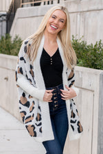 "Miss Sparkling  This knit leopard print cardigan had just the right amount of print to keep you warm and trendy this winter.  Collection: Winter 2020 Color: White - Leopard Print Neckline: Open Sleeve: Long Sleeve 35% cotton 65% polyester Style #: O205029 Contact us for any additional measurements or sizing.  Melissa is 5'5"" and wears a 0 in jeans, small top and size 6 shoe. She is wearing a size small in this top."
