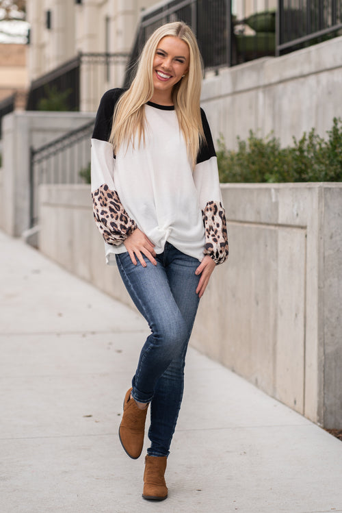 "Miss Sparkling  This waffle knit white top with leopard belle sleeves had just the right amount of print to keep you warm and trendy this winter.  Collection: Winter 2020 Color: Color Block - Leopard Neckline: Round Neck Sleeve: Long Sleeve 35% cotton 65% polyester Style #: US00459  Contact us for any additional measurements or sizing.  Melissa is 5'5"" and wears a 0 in jeans, small top and size 6 shoe. She is wearing a size small in this top."