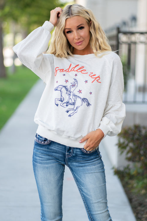 Miss Me  Collection: Fall 2020 Saddle Up Cowgirl Sweater Color: White with Red & Black Graphics Neckline: Round Sleeve: Half Puff Sleeve 65% Polyester, 30% Cotton, 5% Spandex; Contrast: 95% Cotton, 5% Spandex Style #: MJT0018L-Off White Saddle up for the cutest sweater you'll ever see featuring a saddle up graphic print at front, a round neck line, a bishop long sleeves.