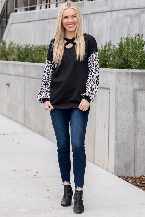"Miss Sparkling  This cozy criss-cross nexk long sleeve top is perfect for dressing up paired with denim and heels.   Collection: Winter 2020 Color: Black Neckline: Criss-Cross V-Neck Sleeve: Long Sleeve 65% cotton 35% polyester Style #: US00093-Black Contact us for any additional measurements or sizing.  Melissa is 5'5"" and wears a 0 in jeans, small top and size 6 shoe. She is wearing a size small in this top."