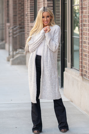 "Hem & Thread   This cozy open cardi sweater can be paired with denim or dressed and will keep you warm and cute.   Collection: Fall 2020 Color: Heather Grey Neckline: Open Sleeve: Long Sleeve 74% ACRYLIC 22% POLYESTER 4% LYCRA  Style #: 30108W Contact us for any additional measurements or sizing.  Haley is 5'6"" and wears size 25 in jeans, a small top and 7.5 in shoes. She is wearing a size small in this sweater."