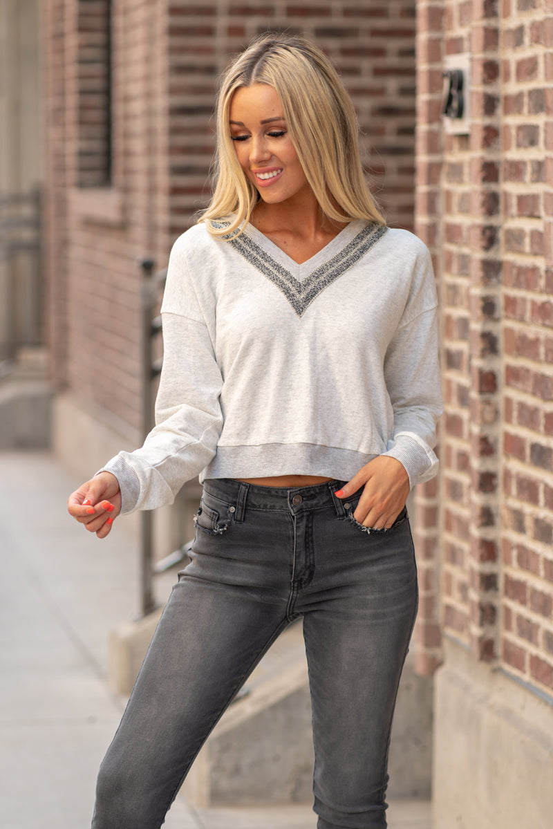 "Hem & Thread   This cozy hoodie will be your best friend this fall. Trendy and comfortable! Perfect to pair with high waist skinny jeans and a pair booties,  Collection: Fall 2020 Color: Grey Neckline: V Neck with Hoodie Sleeve: Long Sleeve 100% COTTON SELF CONTRAST:64% POLYESTER 34% COTTON 2% SPANDEX Style #: 7617F Contact us for any additional measurements or sizing.  Haley is 5'6"" and wears size 25 in jeans, a small top and 7.5 in shoes. She is wearing a small in this top."