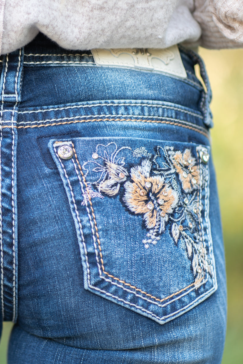 "Miss Me Collection: Fall 2020 Wash: Dark Wash Inseam: 34"" Boot Cut 73% Cotton, 24% Polyester, 3% Elastane Sequin Trim and Rhinestone Rivets  Mid Rise, 8.75"" Front Rise Embellished Floral Pocket Style #: M3585B Contact us for any additional measurements or sizing.  Haley wears a size small top, a 25 in jeans and a small in tops. She is wearing a size 25 in these jeans"