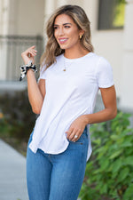 The top is a must-have to wear with every high waist denim. If you like to wear high waist jeans but hate crop tops, this is the perfect tee for you. Pair it with your favorite accessories to dress it up, or keep it casual by itself.   Collection: Core Style Style Name: Split Hem Tee Color: White Cut: Short Sleeve, Split Hem, Round Neck Material: 51%Cotton 49%Modal Style #: AM69411-B4 Contact us for any additional measurements or sizing.
