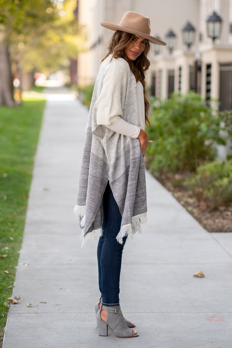 "Hem & Thread   This cozy open cardi sweater can be paired with denim or dress and will keep you warm and cute.   Collection: Fall 2020 Color: Heather Grey Neckline: Open Open Poncho Fit 52% ACRYLIC 28% COTTON 20% POLYESTER Style #: 8515F Contact us for any additional measurements or sizing.  Taylor is 5'7"" and wears a size 3 in jeans, small top and an 8.5 in shoes. She is wearing a size small in this sweater."