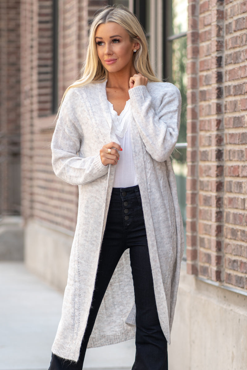 Hem & Thread   This cozy open cardi sweater can be paired with denim or dressed and will keep you warm and cute.   Collection: Fall 2020 Color: Heather Grey Neckline: Open Sleeve: Long Sleeve 74% ACRYLIC 22% POLYESTER 4% LYCRA  Style #: 30108W Contact us for any additional measurements or sizing.  Haley is 5'6