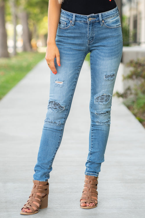 "KanCan Jeans Collection: Fall 2020 Color: Medium Wash Skinny, 29.5"" Inseam  Mid Rise, 8.5"" Front Rise Leopard Patch Backed Distress  92% Cotton 6% Polyester 2% Spandex  Fly: Zipper Style #: KC6307D Contact us for any additional measurements or sizing."