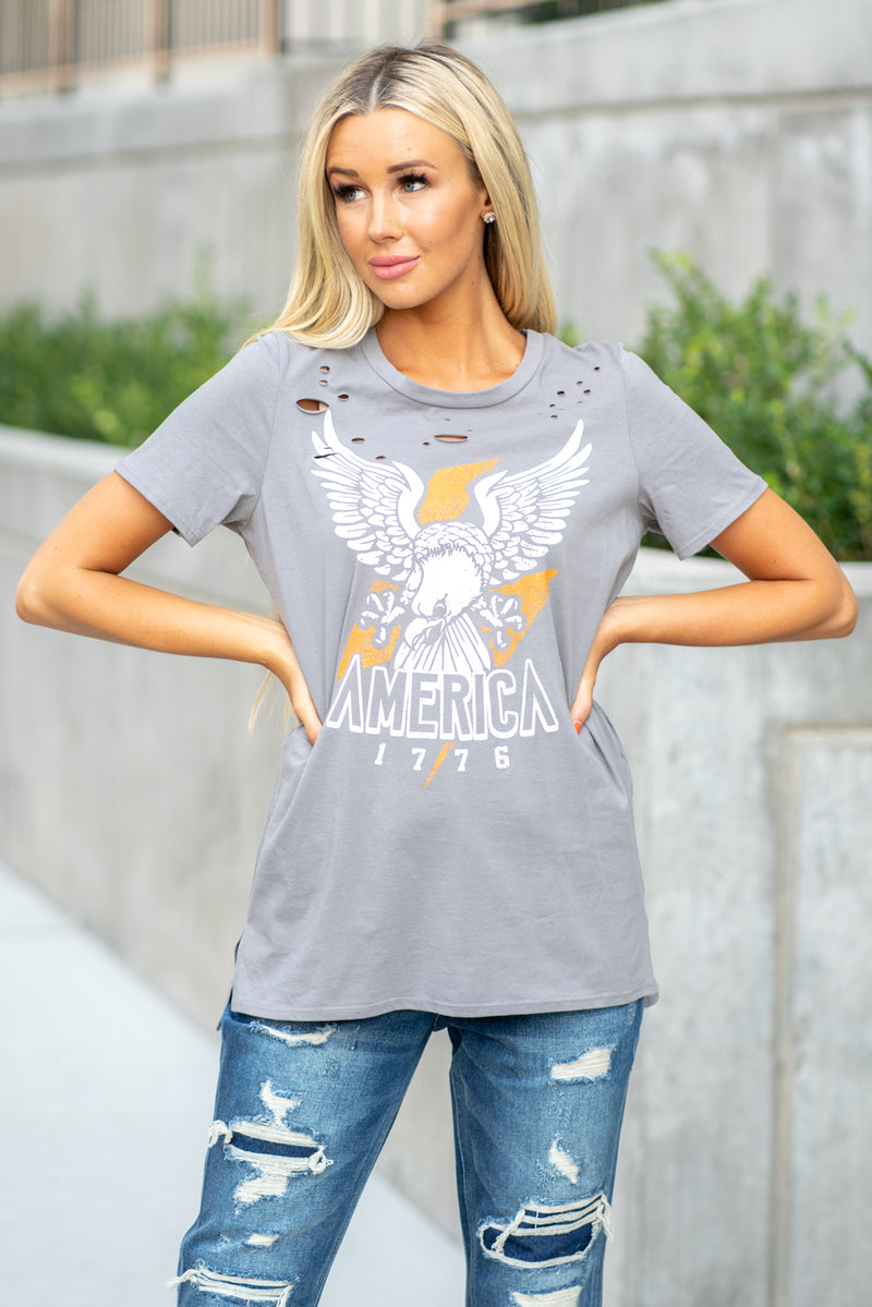 "Zutter  You know the saying, proud to be and American! The distressed tee is great paired with denim and a pair of tennis shoe.  Collection: Fall 2020 Color: Charcoal Grey Neckline: Round Sleeve: Short Material: 100% Cotton Style #: F395-7252 Contact us for any additional measurements or sizing.  Haley is 5'6"" and wears size 25 in jeans, a small top and 7.5 in shoes. She is wearing a 25 in these jeans."
