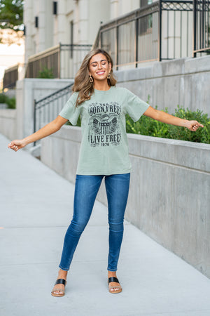 "Zutter  America, Born Free & Live Free... Show your patriotic pride in this cute tee.  Collection: Fall 2020 Color: Olive Green Neckline: Round Sleeve: Short Material:100% Cotton Style #: F8958-1410 Contact us for any additional measurements or sizing.  Taylor is 5'7"" and wears a size 3 in jeans, small top and an 8.5 in shoes. She is wearing a size small in this top."