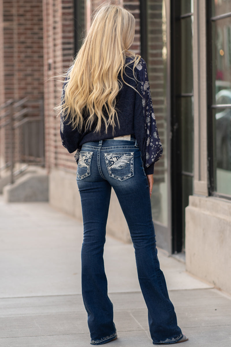 "Miss Me Collection: Fall 2020 Wash: Dark Blue Inseam: 34"" Boot Cut 93% Cotton 6% Polyester 1% Elastane Mid Rise, 8.75"" Front Rise Embellished Feather Pocket  Style #: M3659B Contact us for any additional measurements or sizing.  Haley wears a size small top, a 3 in jeans and a small in tops. She is wearing a size 26 in these jeans."