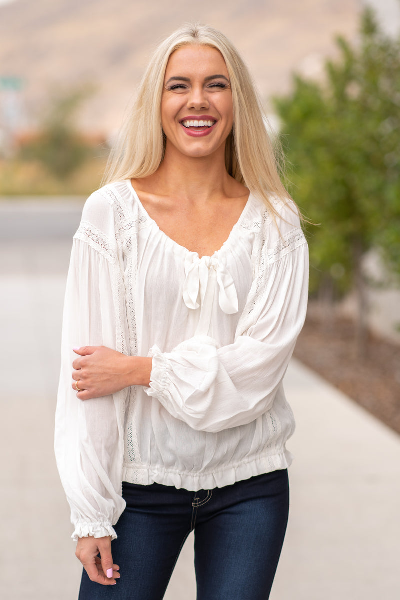 "Hem & Thread   This long sleeve lace trimmed top is great for dressing up your favorite pair of jeans. Wear with heels are you are ready for a night out!  Collection: Fall 2020 Color: Ivory White Tie Front, Synched Sleeves & Waistband Neckline: Round Neck Sleeve: Long Sleeve 100% Rayon Style #: 30056 Contact us for any additional measurements or sizing.  Melissa is 5'5"" and wears a 2 in jeans, small top and size 6 shoe. She is wearing a size small in this top."
