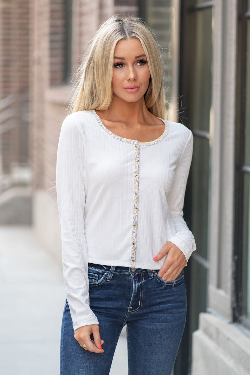 Hem & Thread   Button up in fall floral with this cute ripped top that is perfect to pair with high waist denim. Feel pretty and cozy!  Collection: Fall 2020 Color: Ivory White Neckline: Round neckline, button down Sleeve: Long Sleeve 64% POLYESTER 28% COTTON 8% SPANDEX Style #: 8026W Contact us for any additional measurements or sizing.  Haley is 5'6