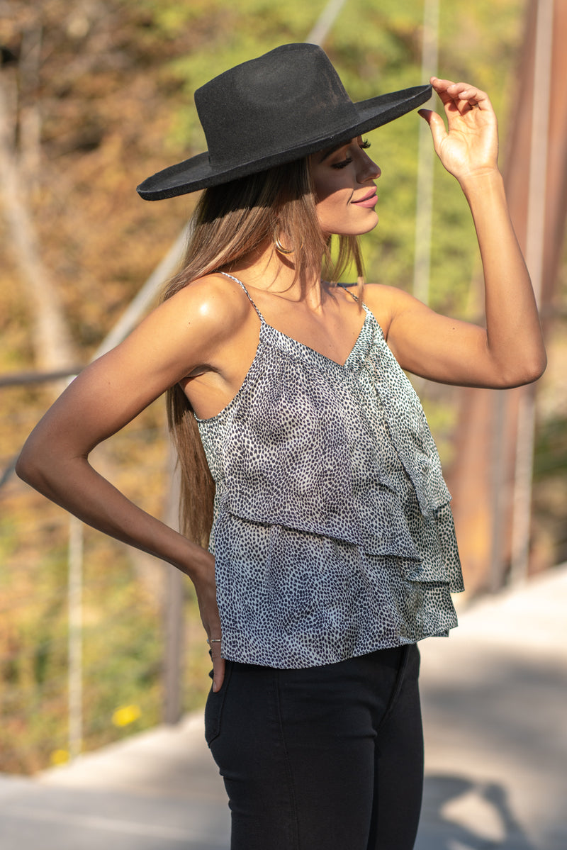 "Slip into sweet new tops with this adorable cami featuring an all over print, ruffle detailing throughout, a slight v-neck line, adjustable spaghetti straps, and a flowy fit. Collection: Fall 2020 Color: Grey Neckline: V Neck Sleeve: Cami Tank 100% Polyester  Style #: MHT0119T Contact us for any additional measurements or sizing.  Taylor is 5'7"" and wears a size 3 in jeans, small top and an 8.5 in shoes. She is wearing a size small in this tank."