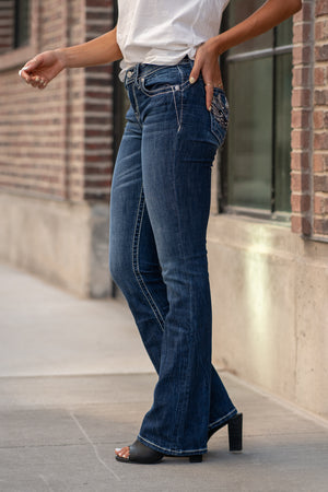 "Miss Me Collection: Fall 2020 Wash: Dark Blue Inseam: 34"" Boot Cut 99% Cotton, 1% Elastane Sequin Trim and Rhinestone Rivets  Mid Rise, 8.75"" Front Rise Embellished Silver Angels Wings Style #: M3654B Contact us for any additional measurements or sizing.  Taylor is 5'7"" and wears a size 4 in jeans, small top and an 8.5 in shoes. She is wearing a size 25 in these jeans."