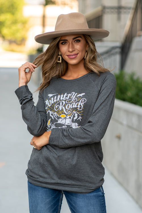 "Zutter  Country Road, take me home. This cute graphic pull over will be the coziest piece in your closet.  Collection: Fall 2020 Color: Black Neck: Round Sleeve: Long Sleeves Material: French Terry, 95% Rayon 5% Spandex Style #: F246-7219 Contact us for any additional measurements or sizing.  Taylor is 5'7"" and wears a size 3 in jeans, small top and an 8.5 in shoes. She is wearing a size small in this top."