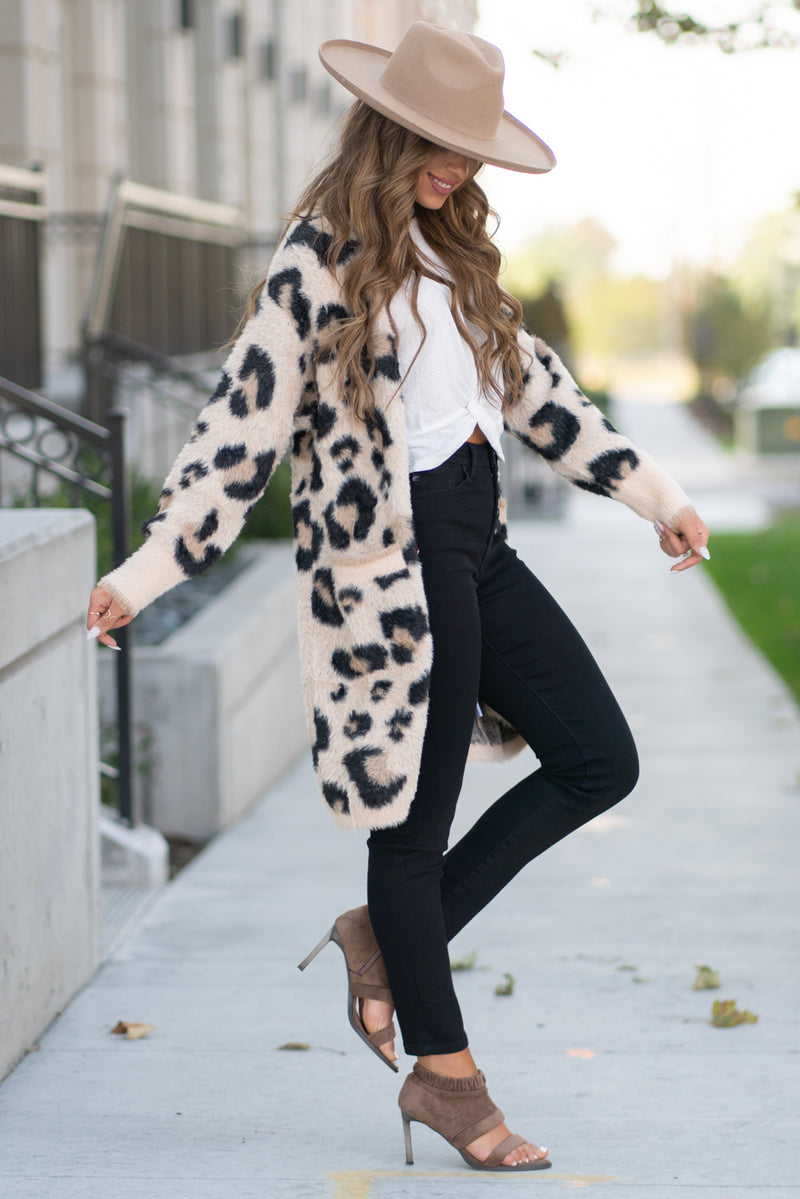 "Miss Me  This oversized long cardigan is ultra soft and will keep you warm.  Collection: Fall 2020 Cozy Up Color: Leopard Beige Sleeve: Long Style #: MSW0174L Contact us for any additional measurements or sizing.  Taylor is 5'7"" and wears a size 3 in jeans, small top and an 8.5 in shoes. She is wearing a size small in this sweater."