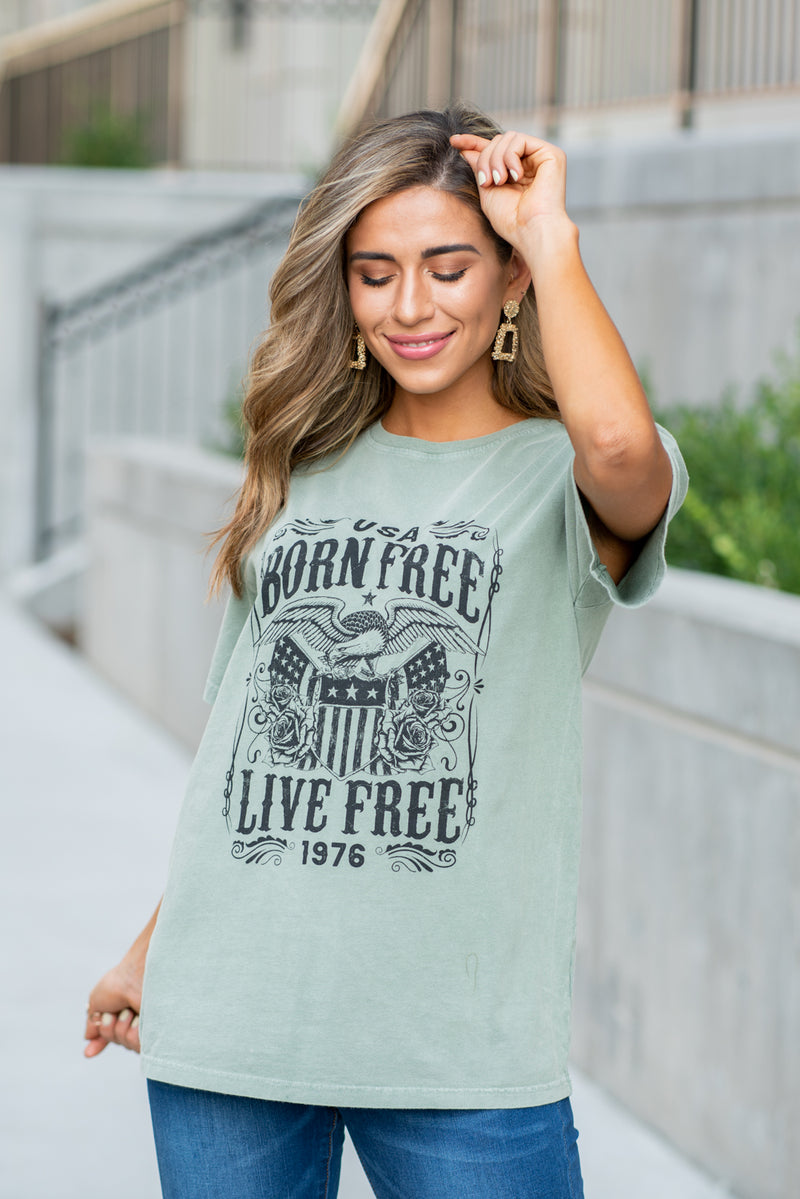 Zutter  America, Born Free & Live Free... Show your patriotic pride in this cute tee.  Collection: Fall 2020 Color: Olive Green Neckline: Round Sleeve: Short Material:100% Cotton Style #: F8958-1410 Contact us for any additional measurements or sizing.  Taylor is 5'7
