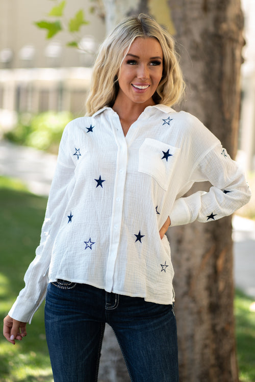 "Hem & Thread   Light and easy, this linen button down top will be your favorite to pair with denim. Show your American pride with the cute embroidered stars.   Collection: Fall 2020 Color: White Neckline: Collar neckline with a button down front Sleeve: Long Sleeve 100% Cotton Style #: 7744W Contact us for any additional measurements or sizing.  Haley is 5'6"" and wears size 3 in jeans, a small top and 7.5 in shoes. She is wearing a size small in this top."