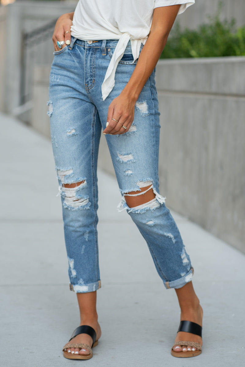 "KanCan Jeans Collection: Fall 2020 Color: Medium Wash Ankle Skinny, 27"" Inseam  High Rise, 9.5"" Front Rise Super Distressed Legs 100% Cotton Fly: Zipper Style #: KC9187M Contact us for any additional measurements or sizing.  Taylor is 5'7"" and wears a size 4 in jeans, small top and an 8.5 in shoes. She is wearing a size 25 in these jeans."