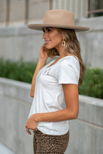 "Show off your country sass in this cute Miss Me v neck graphic tee shirt. adorned with a chain necklace with charms including a cowboy hat, boots horse and horseshoe.  Collection: Fall 2020 Color: White Neckline: V Neck Sleeve: Short 100% Cotton  Style #: MTJ0078S Contact us for any additional measurements or sizing.  Taylor is 5'7"" and wears a size 3 in jeans, small top and an 8.5 in shoes. She is wearing a size small in this top."