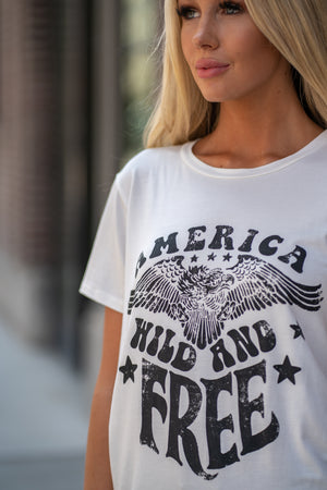 "Zutter  America, Wild & Free. Yes please! Show your patriotic pride in this cute tee.  Collection: Fall 2020 Color: Ivory White Neckline: Round Sleeve: Short Material: 95% Rayon 5% Spandex Style #: F201-0817 Contact us for any additional measurements or sizing.  Haley is 5'6"" and wears size 25 in jeans, a small top and 7.5 in shoes. She is wearing a size small in this top."