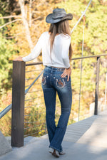 "Miss Me Collection: Fall 2020 Wash: Dark Wash Inseam: 34"" Boot Cut  Sequin Trim and Rhinestone Rivets  Mid Rise, 8.75"" Front Rise Embellished Cowboy on a Horse Pocket Style #: M3676B Contact us for any additional measurements or sizing.  Taylor is 5'7"" and wears a size 4 in jeans, small top and an 8.5 in shoes. She is wearing a size 26 in these jeans."