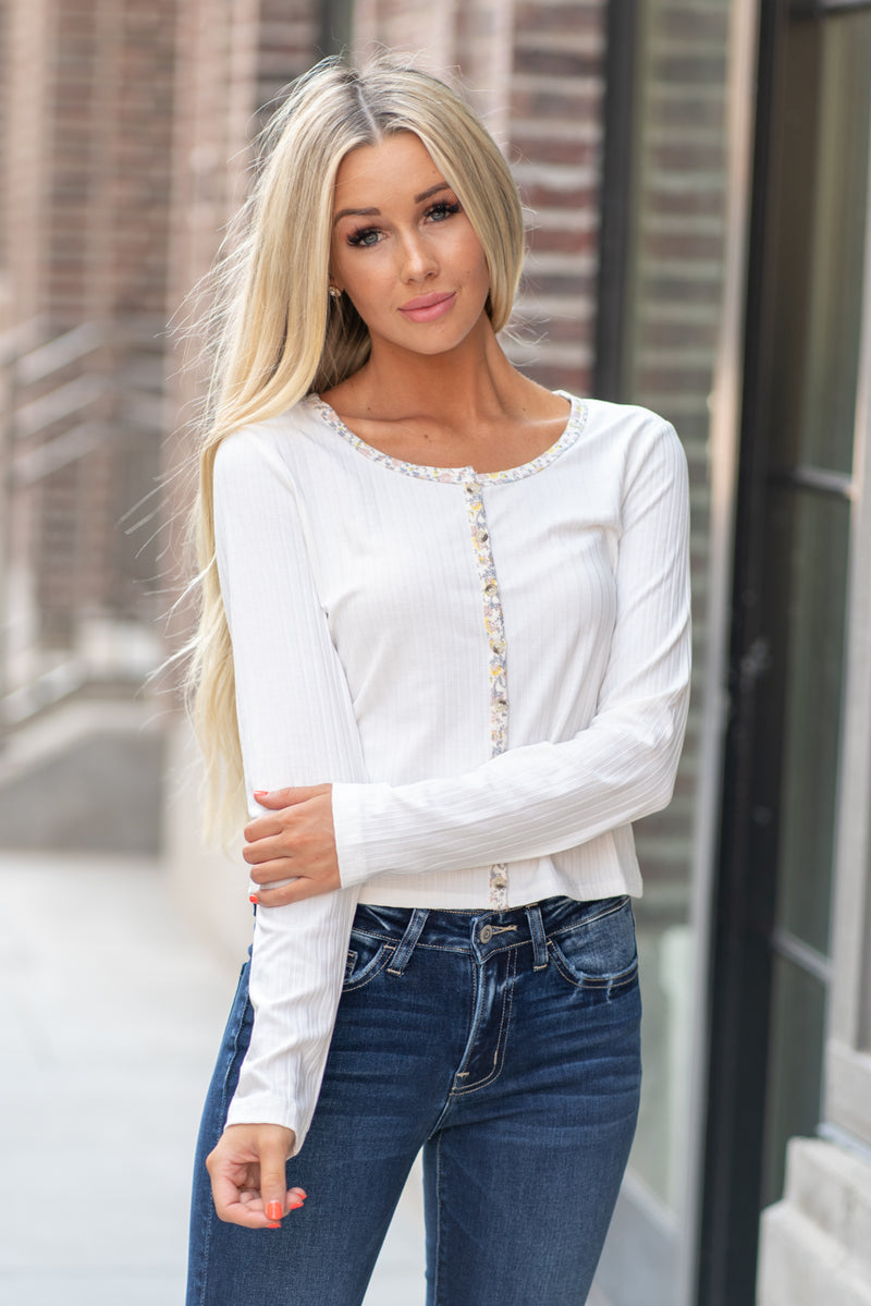 "Hem & Thread   Button up in fall floral with this cute ripped top that is perfect to pair with high waist denim. Feel pretty and cozy!  Collection: Fall 2020 Color: Ivory White Neckline: Round neckline, button down Sleeve: Long Sleeve 64% POLYESTER 28% COTTON 8% SPANDEX Style #: 8026W Contact us for any additional measurements or sizing.  Haley is 5'6"" and wears size 25 in jeans, a small top and 7.5 in shoes. She is wearing a size small in this top."