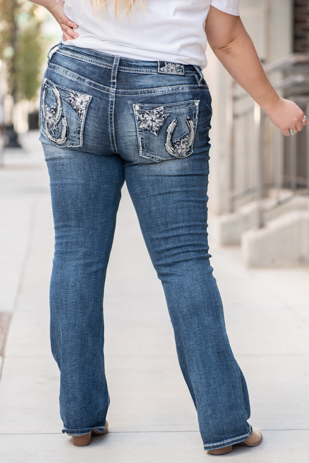 "Miss Me Collection: Fall 2020 Wash: Dark Blue Inseam: 34"" Boot Cut 97% Cotton, 3% Elastane Mid Rise, 8.75"" Front Rise Embellished Floral Horseshoe Pockets  Style #: M3644B Contact us for any additional measurements or sizing.  Victoria is wearing a size 36 in these jeans."