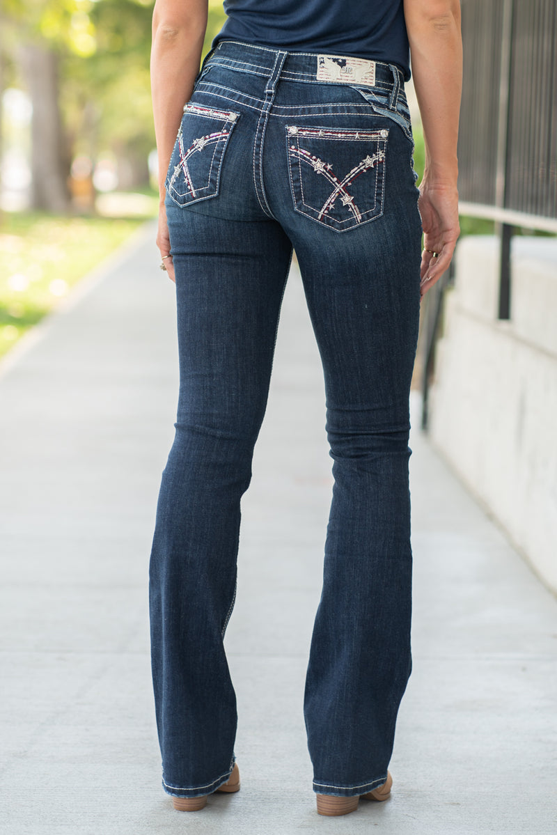 "Miss Me Collection: Fall 2020 Wash: Dark Blue Front Rise: 9 1/2"" ; Back Rise: 14"" Inseam: 34"" Boot Cut Mid Rise, 8.75"" Front Rise Embellished American Stars & Striped Style #: M3444B20  Contact us for any additional measurements or sizing.  Chloe is 5'8"" and 130 pounds. She wears a size 3 in jeans, a small top and 8.5 in shoes. She is wearing a 26/3 in these jeans."